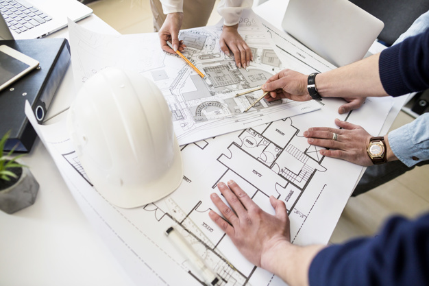 architects-engineer-discussing-table-with-blueprint_23-2147842977